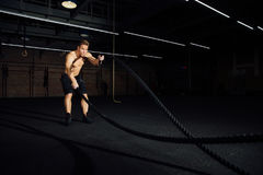 Fitness man workout with battle ropes at gym. training exercise fitted body in club. Torso. Stock Photos