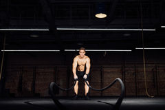 Fitness man workout with battle ropes at gym. training exercise fitted body in club. Torso. Stock Photo