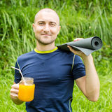Fitness man with yoga mat holding a glass of orange juice Royalty Free Stock Images