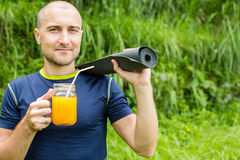 Fitness man with yoga mat holding a glass of orange juice Stock Photos