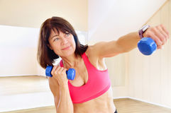 Fitness mature woman working out with dumbbells Royalty Free Stock Image