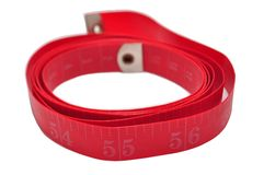 Fitness Measuring Tape. Red fitness Measuring Tape rolled into a circle with the clear number 55 up front and in focus with the background slightly out of focus royalty free stock image