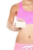 Fitness meisje in sportuitrusting die adreskaartje tonen Stock Afbeelding