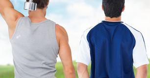 Fitness men back making fitness exercises against countryside background. Digital composite of Fitness men back making fitness exercises against countryside Royalty Free Stock Photography