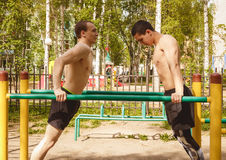 Fitness men at the bar. Exercising outdoors in the Park. Street workout. Fitness men at the bar. Exercising outdoors in the Park. Street workout royalty free stock photography