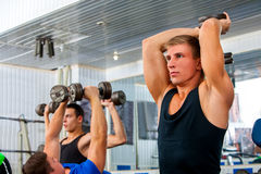 Fitness men friends in gym workout weights with equipment. Stock Image