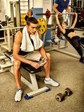 Fitness men friends in gym workout weights with equipment. Muscle men with bottle water dumbbell background workout with barbell at gym. Man and women keeps stock images