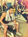 Fitness men friends in gym workout weights with equipment. Muscle men with bottle water dumbbell background workout with barbell at gym. He watches his figure royalty free stock photography