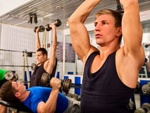 Fitness men friends in gym workout weights with equipment. Stock Photos