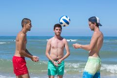 Fitness men playing volley ball at beach. Fitness men playing volley ball at the beach Royalty Free Stock Images