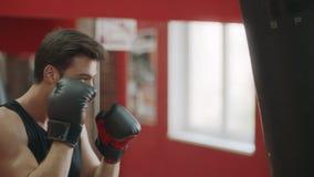 Fitness mens de schop van de opleidingsdoos in sportclub Bokser het schoppen in dozen doende zak in handschoenen stock footage