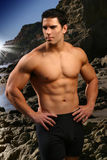 Fitness model. Young male fitness model at the beach with rocks and blue sky Stock Photos