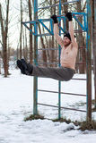 Fitness model doing abdominal press exercise outdoors. A young bearded man in a black hat with naked torso doing street workout - leg raise hanging on the stock images