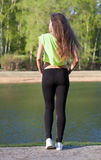Fitness model the good figure costs on the bank of the lake in the summer at sunset. Back. Short top sports pants. Royalty Free Stock Photo