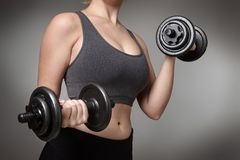 Fitness model on gray background. Close up of a woman middrifed using dumbbells Stock Photography