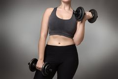 Fitness model on gray background. Close up of a woman middrifed using dumbbells Stock Photo