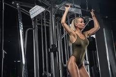 Free Fitness Model In A Swimsuit Posing In A Modern Gym. Blonde. Idial Body Muscles. Beautiful Sportswear. Dark Background. Stock Photo - 133400950