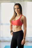 Fitness model indoor. Attractive fitness model in bra and yoga pants posing indoor Stock Image