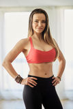 Fitness model indoor. Attractive fitness model in bra and yoga pants posing indoor royalty free stock photos