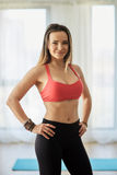Fitness model indoor. Attractive fitness model in bra and yoga pants posing indoor Stock Images