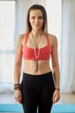Fitness model indoor. Attractive fitness model in bra and yoga pants posing indoor royalty free stock photo