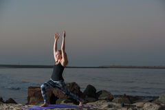Fitness model performs side reaching lunge. Wide view of Yoga Crescent Moon pose on the jetty rocks at night stock images