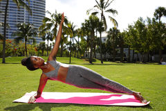 Fitness model planking on a yoga mat in the park Stock Images