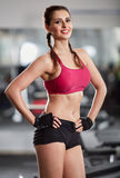Fitness model posing in gym Stock Images