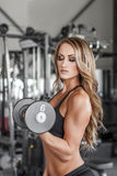 Fitness model pumping up muscles Royalty Free Stock Photography