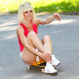 Fitness model on a skateboard. Young athletic girl rides sitting on a skateboard Stock Photos