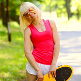 Fitness model on a skateboard. Young athletic girl rides sitting on a skateboard Royalty Free Stock Image
