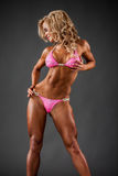 Fitness model. Smiling athletic woman in pink bikini showing muscles on dark background Stock Image