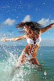 Fitness Model Splashing in Ocean. Fitness model splashing in the ocean in Honduras Stock Photo
