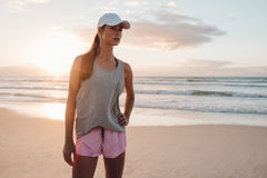Fitness model in sportswear standing on the beach. Shot of fitness model in sportswear standing on the beach with her hand on hip. Healthy young woman on the sea Royalty Free Stock Images