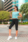 Fitness model standing, wearing sportswear and sunglasses, using phone, listening to music in headphones in city. Stock Images