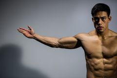 Fitness Model Stretching Out Arm. A fitness model stretches out an arm displaying his bicep muscle Royalty Free Stock Images