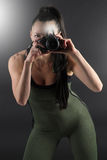 Fitness model taking using a camera to take a photo. Image of a beautiful woman taking a photo wearing a green all in one outfit Stock Image