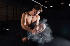 Fitness model trainer rubs his hands with chalk and talc so that fingers do not slip or slide. Black bucket, Strong Clap with Cloud of dust Stock Image