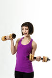 Fitness Model. Weight training with dumbbells but instead of real weight she is using doughnuts as the weights Royalty Free Stock Photo