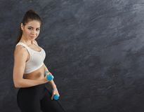 Fitness model woman with dumbbells on grey background stock photography