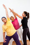 Fitness monitor helping senior ladies in class. Royalty Free Stock Image