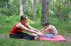 Fitness mother with her 9 years old son. Sports mom with kid doing morning work-out at park. Mum and child do the. Fitness mother with her son. Sports mom with Stock Photos