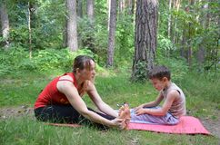 Fitness mother with her 9 years old son. Sports mom with kid doing morning work-out at park. Mum and child do the. Fitness mother with her son. Sports mom with Royalty Free Stock Photo