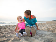 Fitness mother and surprised baby girl on beach Stock Image