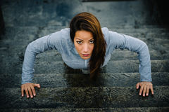 Fitness motivated woman doing urban push ups workout. Urban fitness woman workout doing torso elevated push ups on urban stairs. Motivated strong female athlete Stock Photography