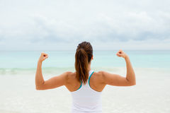 Fitness motivation and success. Strong fitness woman showing arms biceps towards the sea. Healthy lifestyle motivation and success Stock Photo