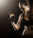 Fitness muscular woman working out with dumbbells Stock Images
