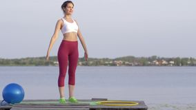 Fitness in nature, attractive girl with beautiful figure performing exercise during sports workout outdoors on bridge. Fitness in nature, attractive girl with stock video footage