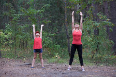 Fitness outdoors mom and daughter Stock Photo