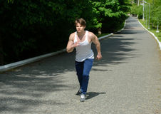 Fitness outdoors. Running sport man. Fit muscular young male runner sprinting at great speed outdoors on road royalty free stock images
